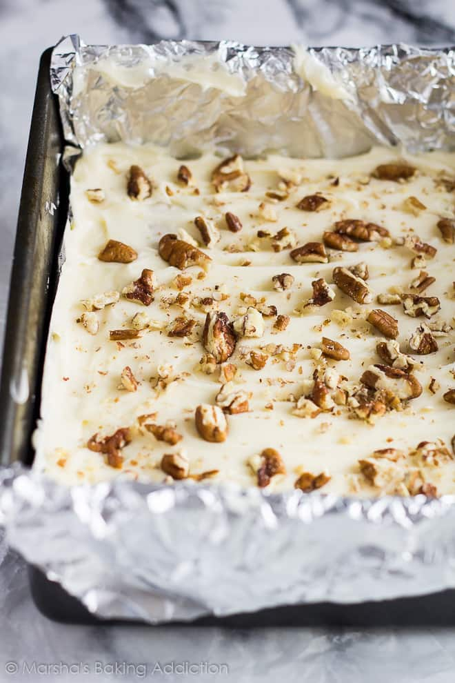 Cream cheese frosted carrot cake blondies in a foil-lined square pan topped with chopped pecans.