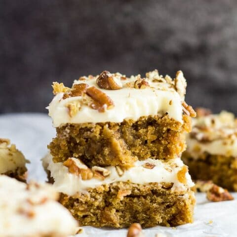 A stack of two cream cheese frosted carrot cake blondies with a bite taken out of the top one on parchment paper.