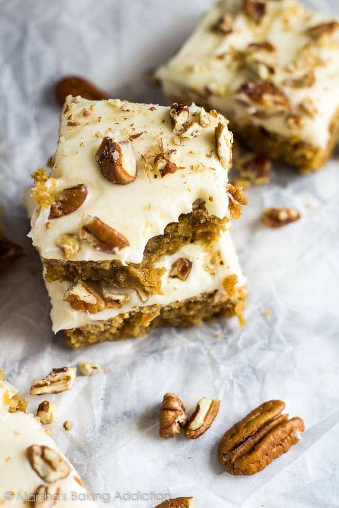 Overhead shot of a stack of two cream cheese frosted carrot cake blondies with a bite taken out of the top one on parchment paper.