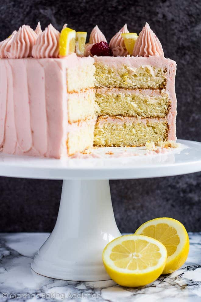 Lemon raspberry layer cake topped with piped swirls, lemon slices and raspberries on a white cake stand with slices removed to show the inside.