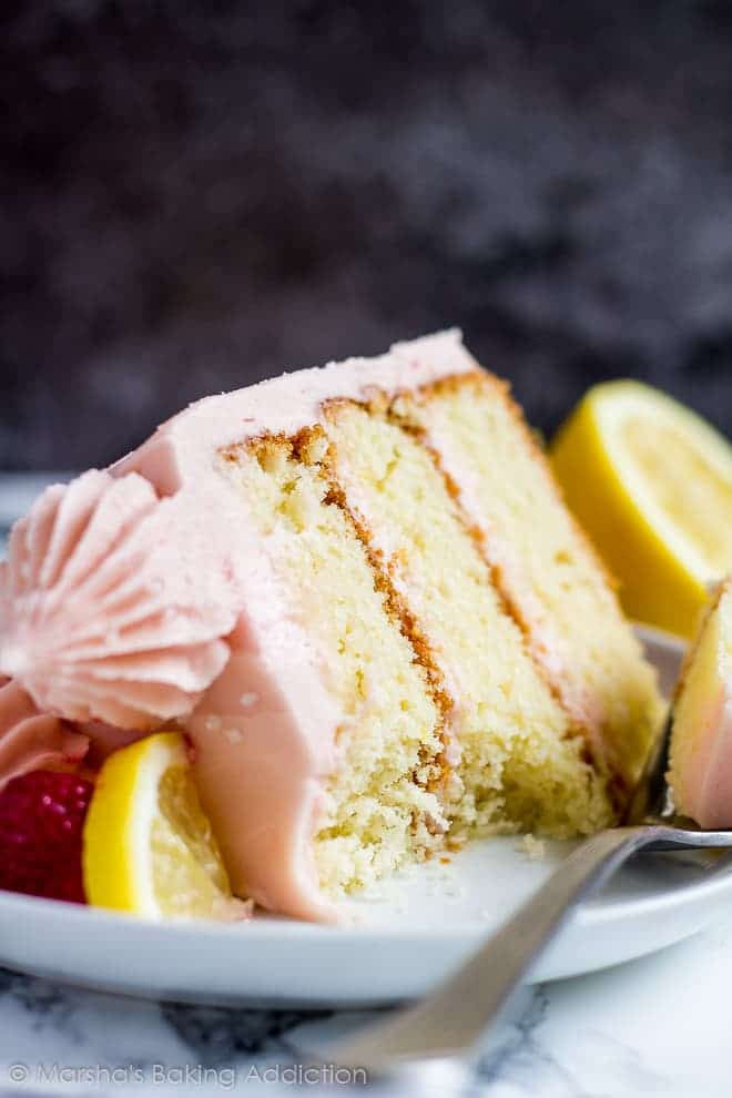 A thick slice of lemon raspberry layer cake served on a small white plate with a fork, slice of lemon and a raspberry.