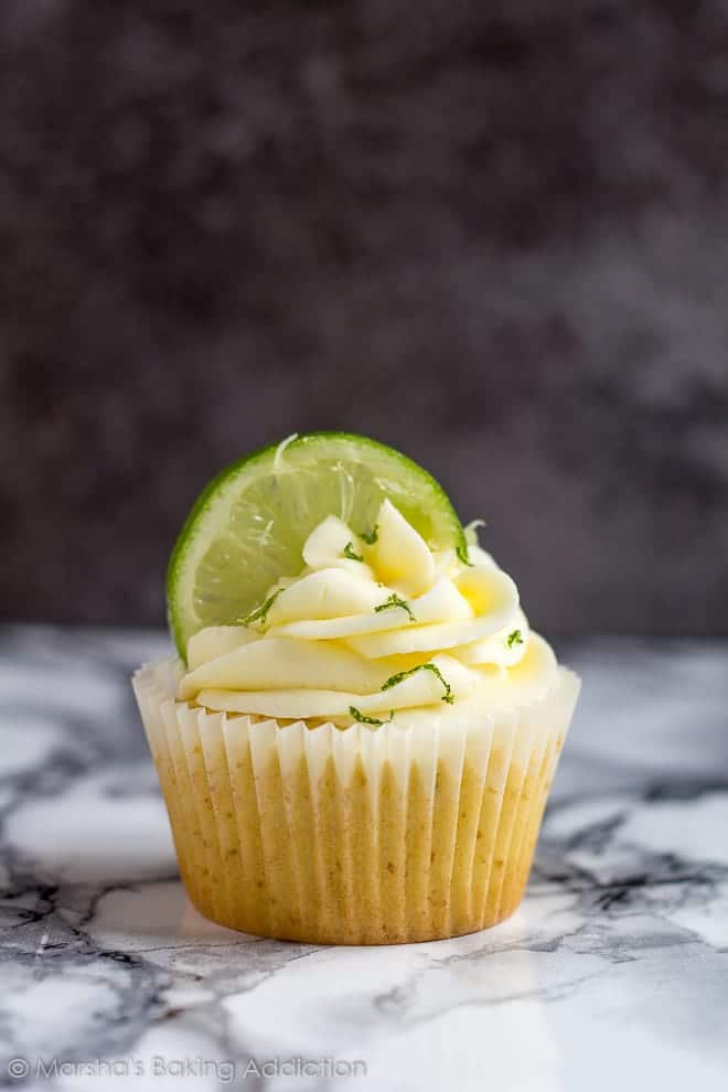 A Margarita cupcake topped with buttercream frosting and a lime slice on marble background.