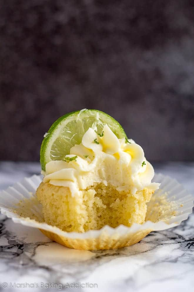 A frosted Margarita cupcake topped with a lime slice with a bite taken out of the cupcake.