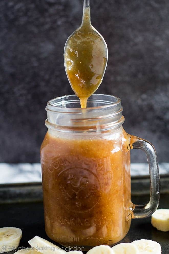 Spoon dunked into a mason jar filled with banana caramel sauce.