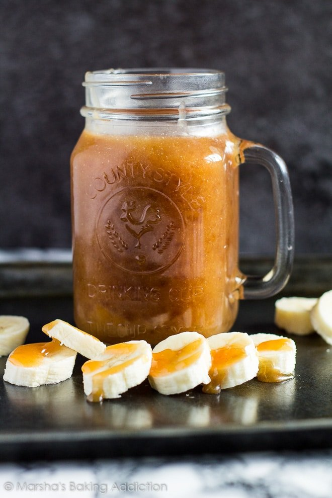 Mason jar filled with homemade banana caramel sauce on a baking tray with banana slices.