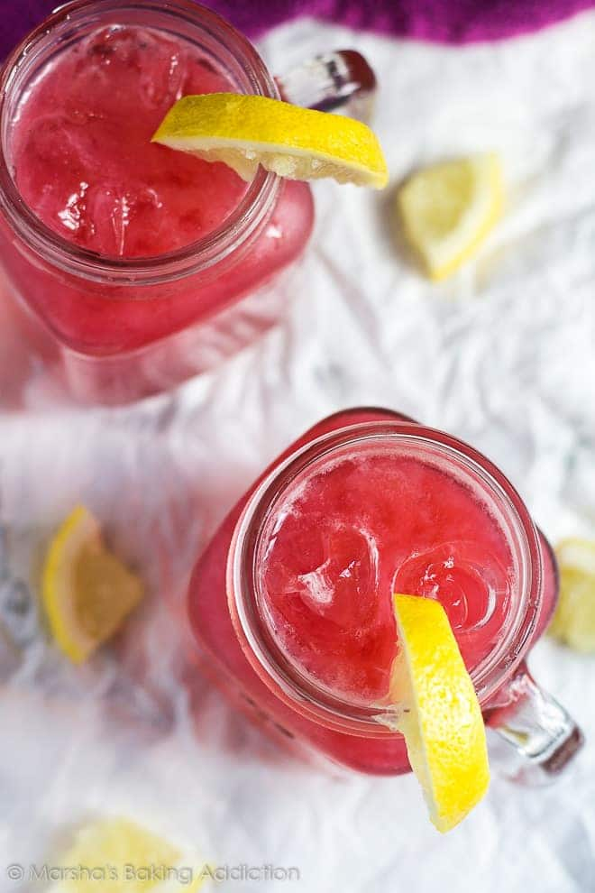 Overhead shot of two mason jars filled with raspberry lemonade with lemon slices on parchment paper.