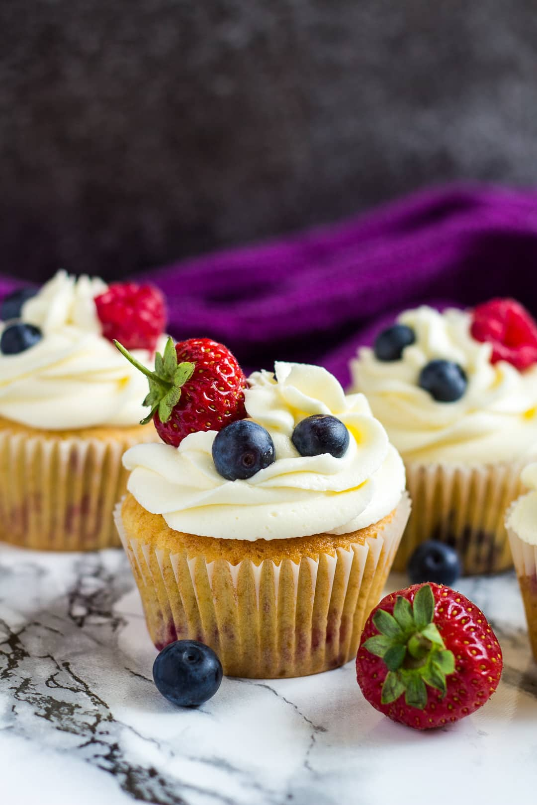 Frosted summer berry cupcakes garnished strawberries and blueberries.