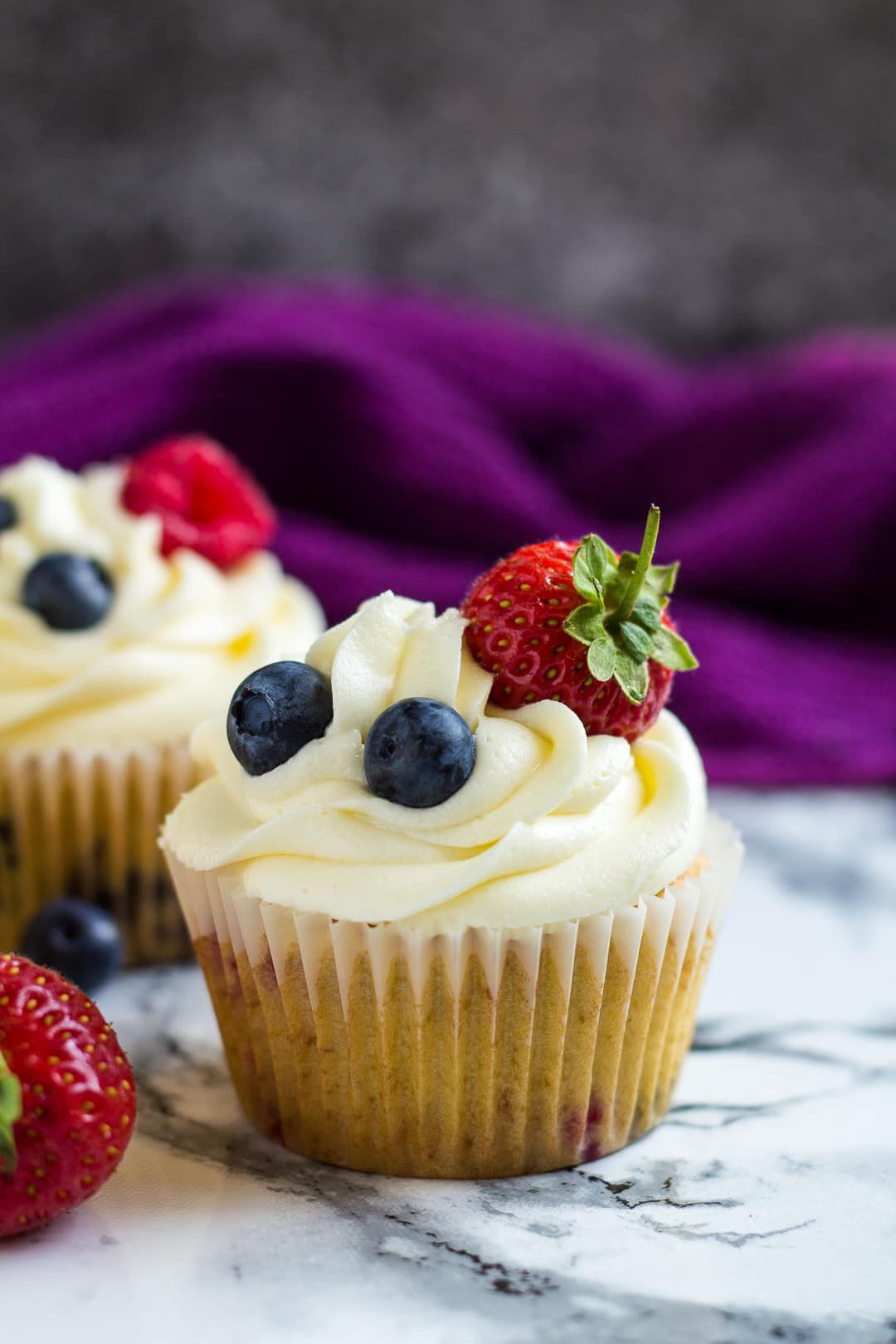 Two frosted cupcakes topped with strawberries and blueberries.