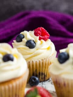 A frosted cupcake topped with raspberries and blueberries.