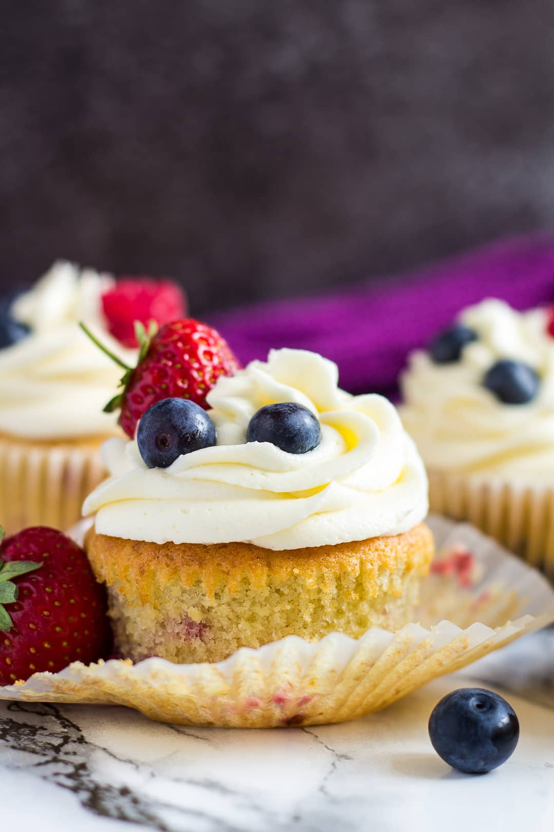 A frosted summer berry cupcake with the wrapper peeled off.