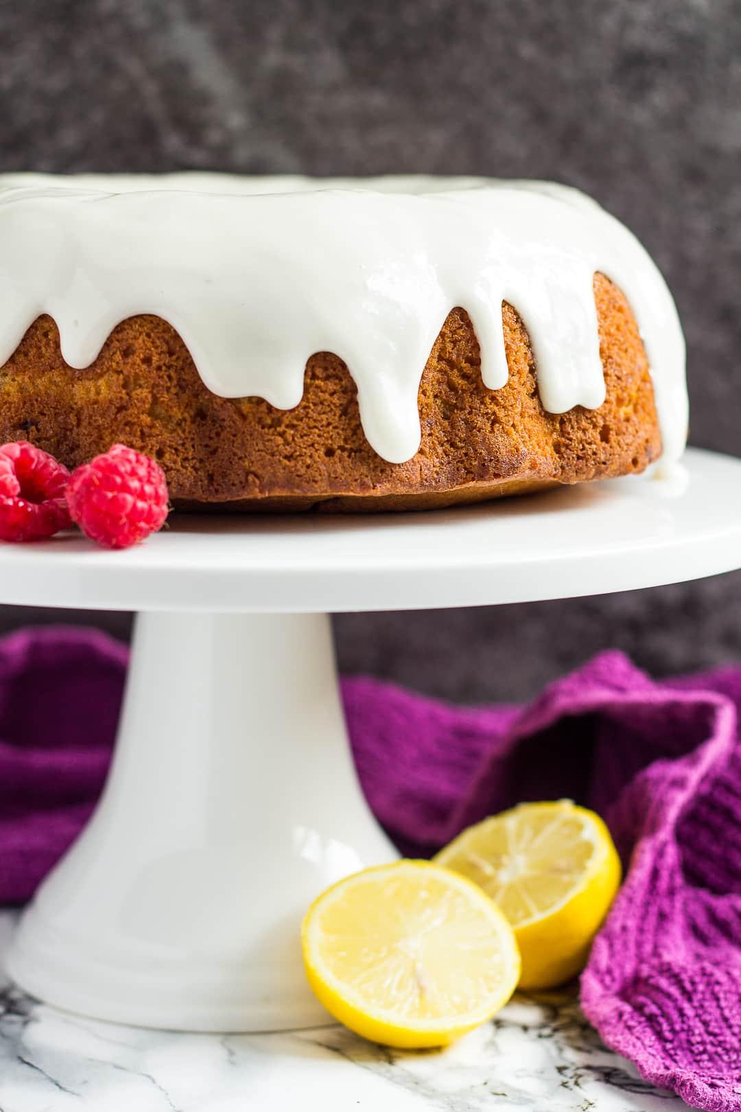 Lemon raspberry bundt cake on a white cake stand.