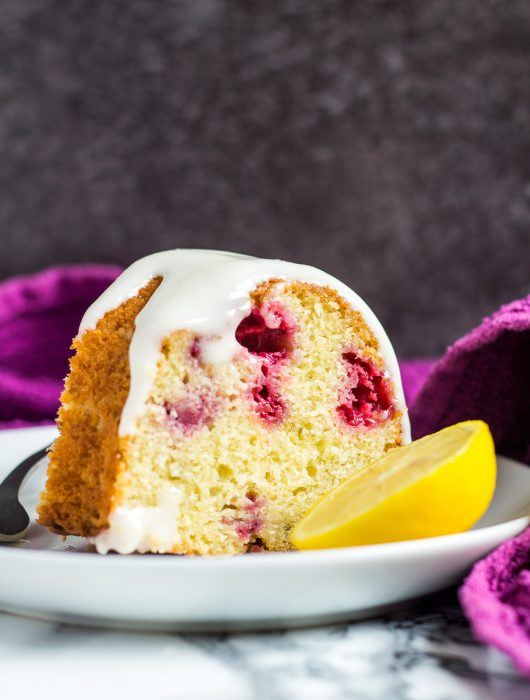 Slice of lemon raspberry bundt cake on a small white plate with a fork.
