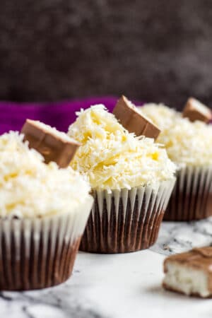 A row of three frosted chocolate coconut cupcakes.