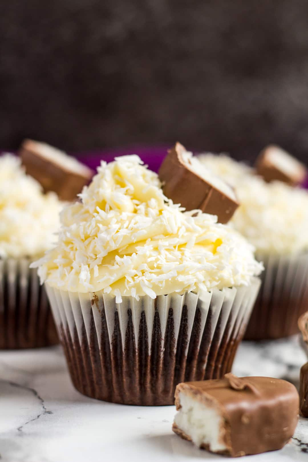 Frosted chocolate coconut cupcakes topped with pieces of Bounty.