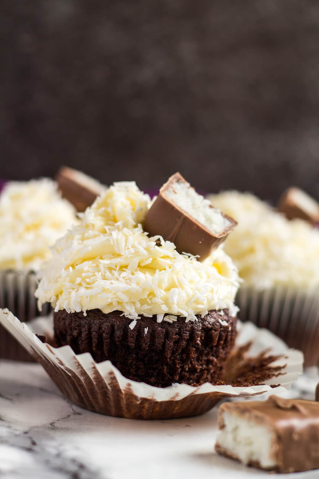 A frosted chocolate coconut cupcake with the wrapper peeled off.
