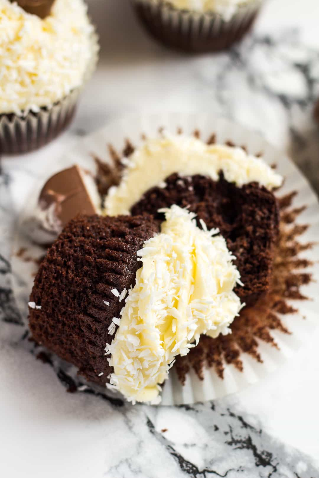 A frosted chocolate coconut cupcake sliced in half on top of wrapper.