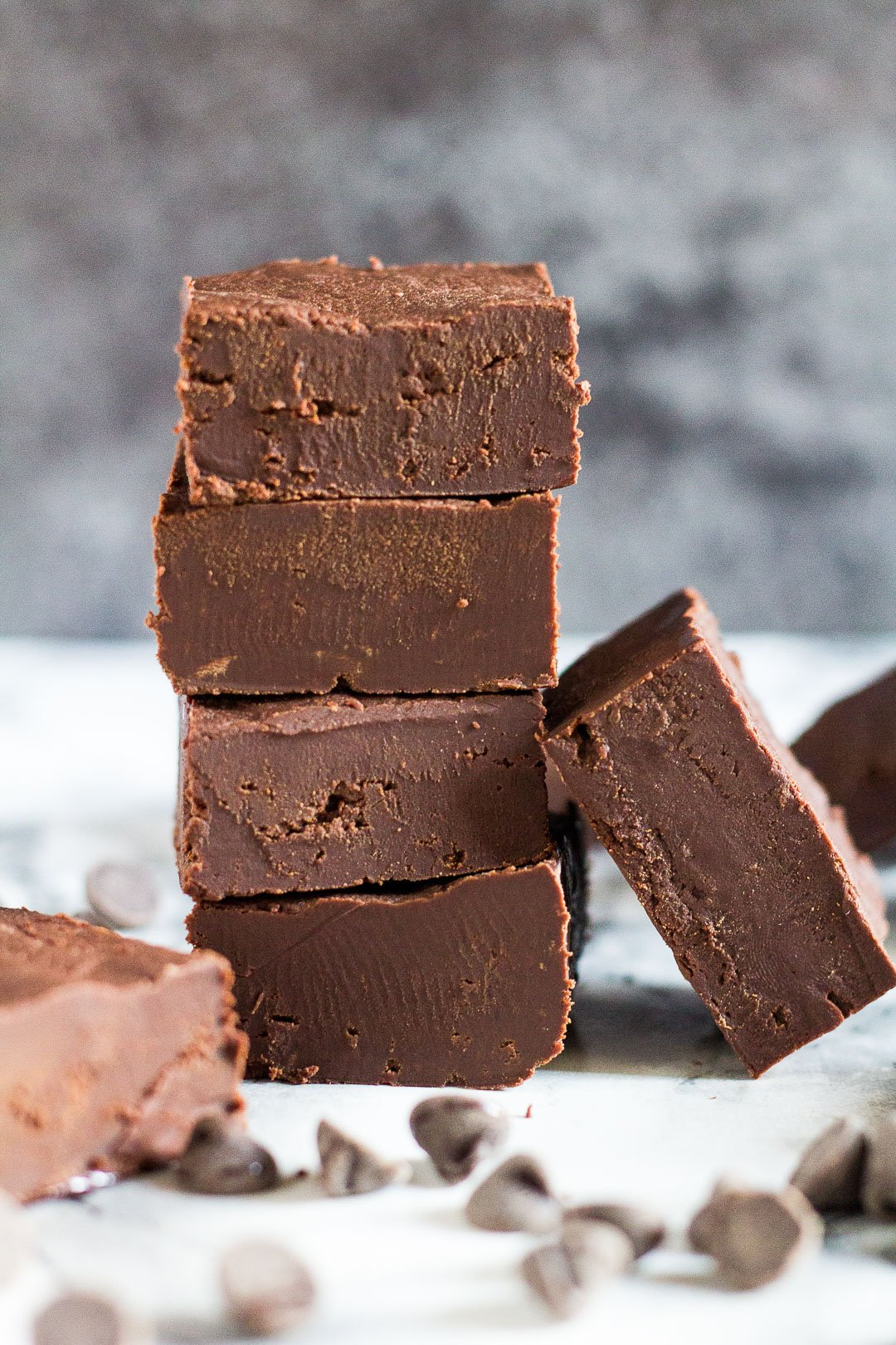 A stack of four pieces of chocolate fudge with one piece leaning up against it.