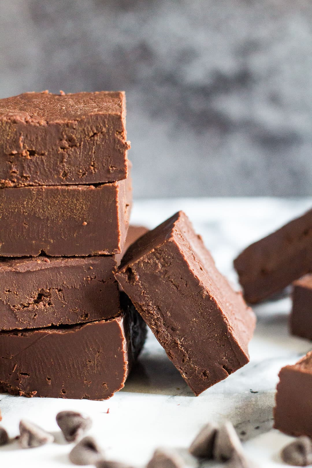 A stack of four pieces of thick chocolate fudge pieces with one piece leaning up against it.