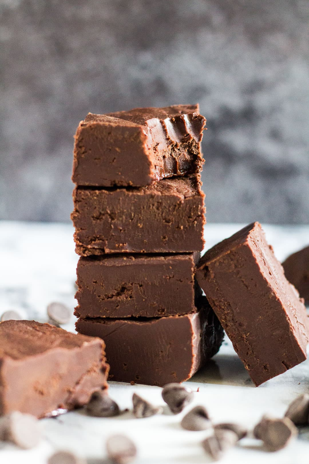 A stack of thick pieces of chocolate fudge with a bite taken out of the top piece.