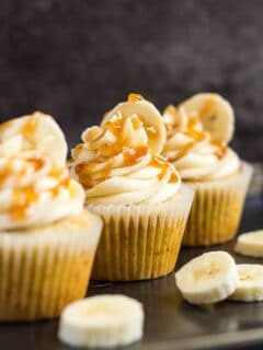 A row of three frosted banana caramel cupcakes on a baking tray with banana slices.