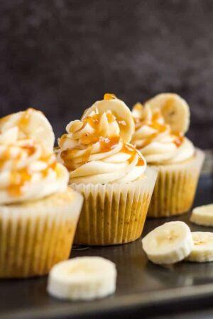 A row of three frosted banana caramel cupcakes on a baking tray with banana slices.