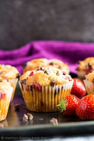 Strawberry chocolate chip muffins on a baking tray with strawberries.