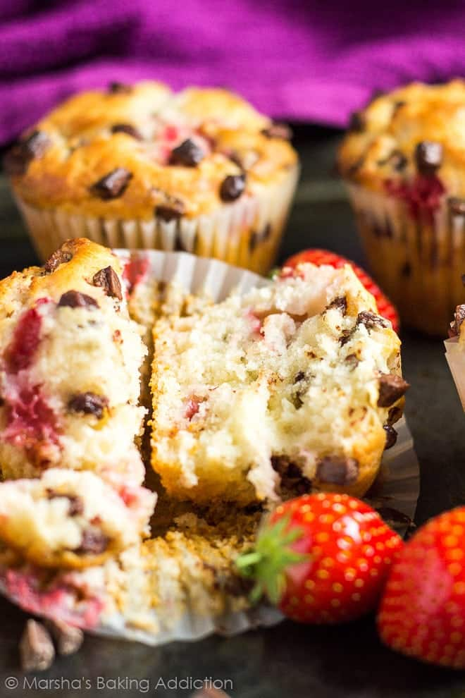 A strawberry chocolate chip muffin cut in half in the wrapper on a baking tray.