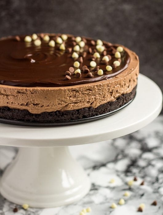 A no-bake chocolate cheesecake topped with chocolate ganache and chocolate chips on a white cake stand.