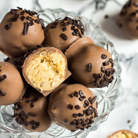 Overhead shot of peanut butter crunch balls in a small glass bowl with one cut in half.
