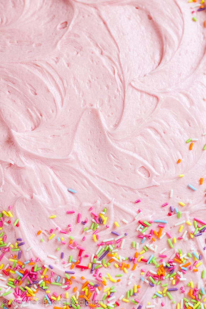 Close-up of pink buttercream frosting with sprinkles on funfetti sheet cake.