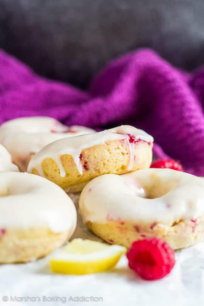 Glazed baked lemon raspberry doughnuts on parchment paper.