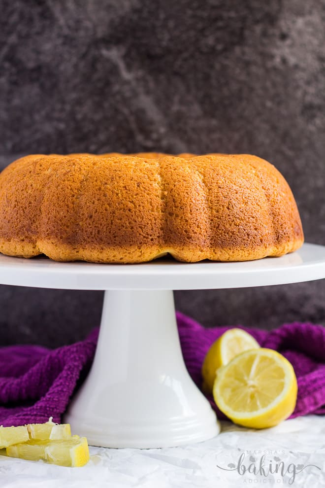 A cheesecake swirl lemon bundt cake with no glaze on a white cake stand.