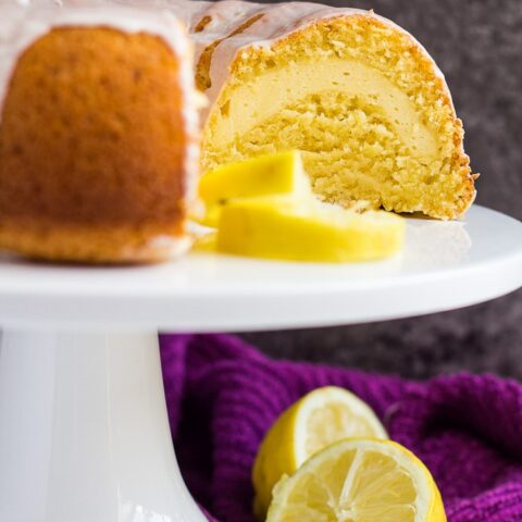 Lemon bundt cake with slices removed to show cheesecake filling on a white cake stand.