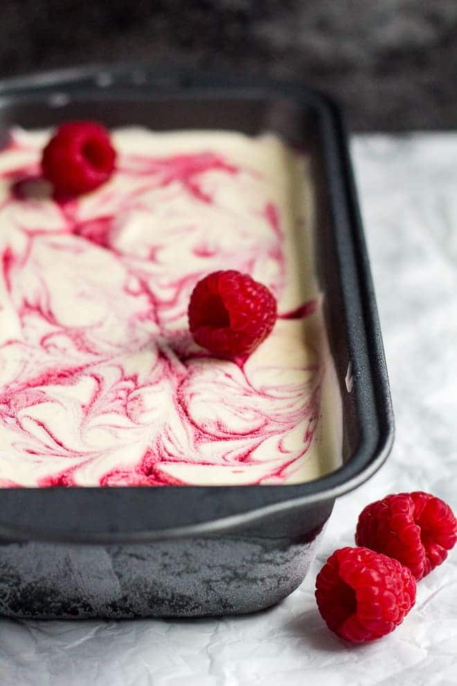 Homemade raspberry ripple ice cream in a loaf pan on parchment paper.