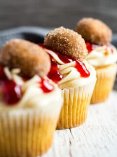 A sideview of a row of three frosted Jam Doughnut Cupcakes.