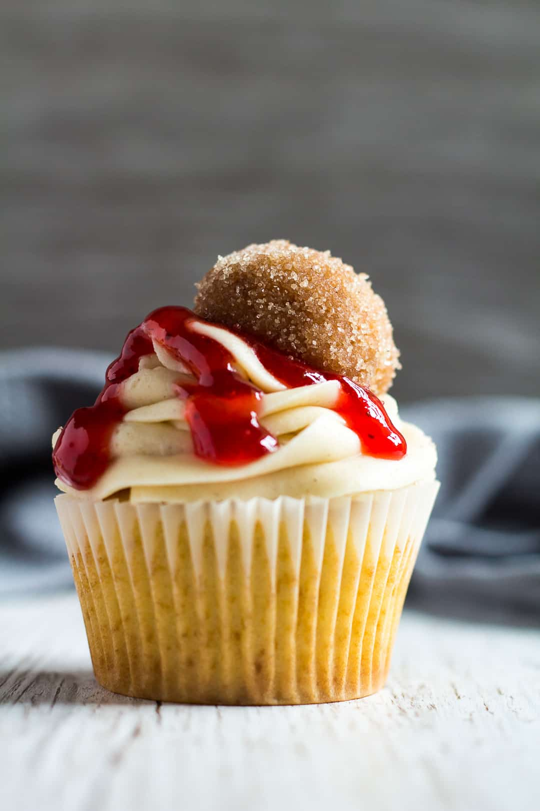 A vanilla cupcake topped with frosting, a drizzle of strawberry jam, and a doughnut hole.