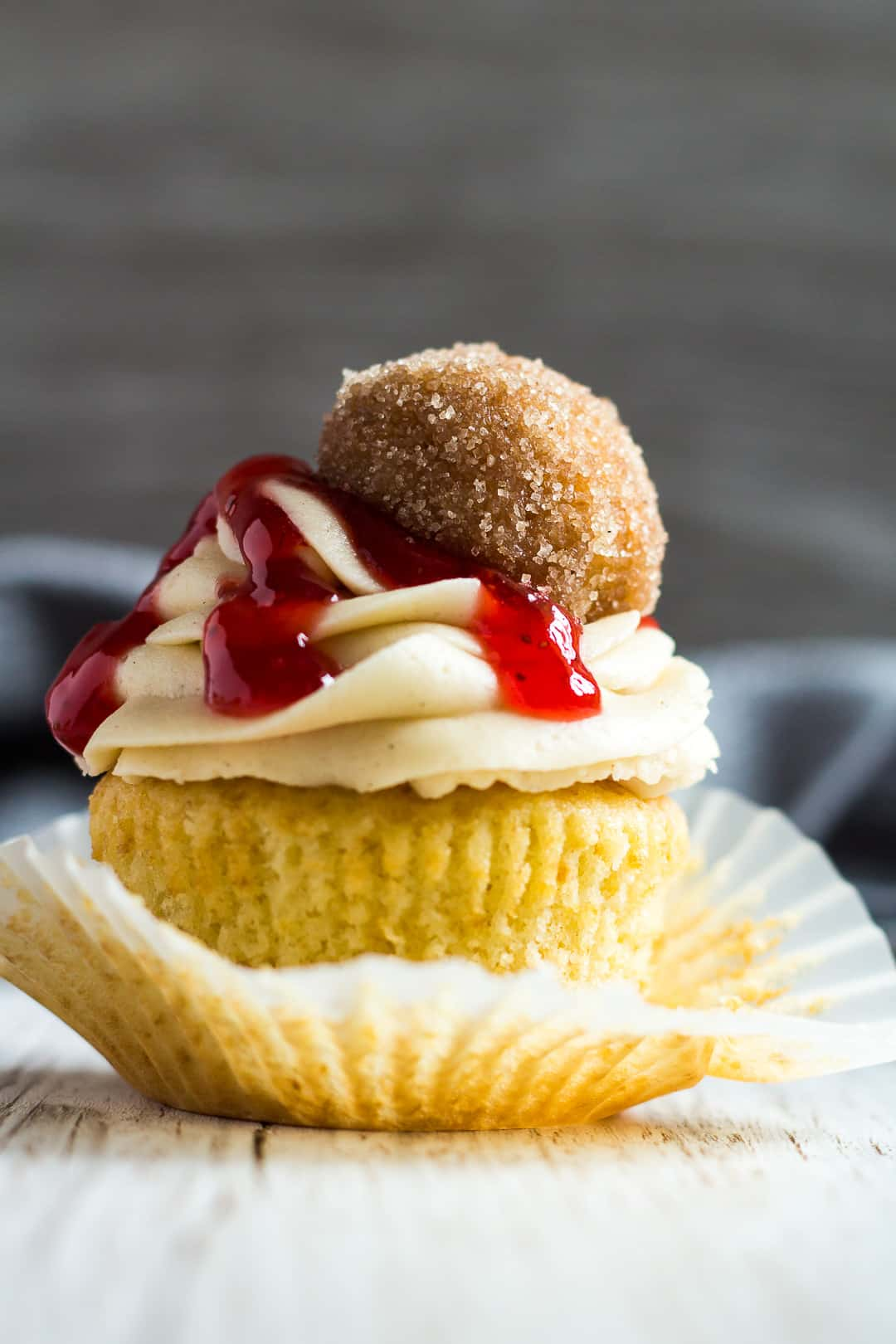 A frosted Jam Doughnut Cupcake with the wrapper peeled off on one side.