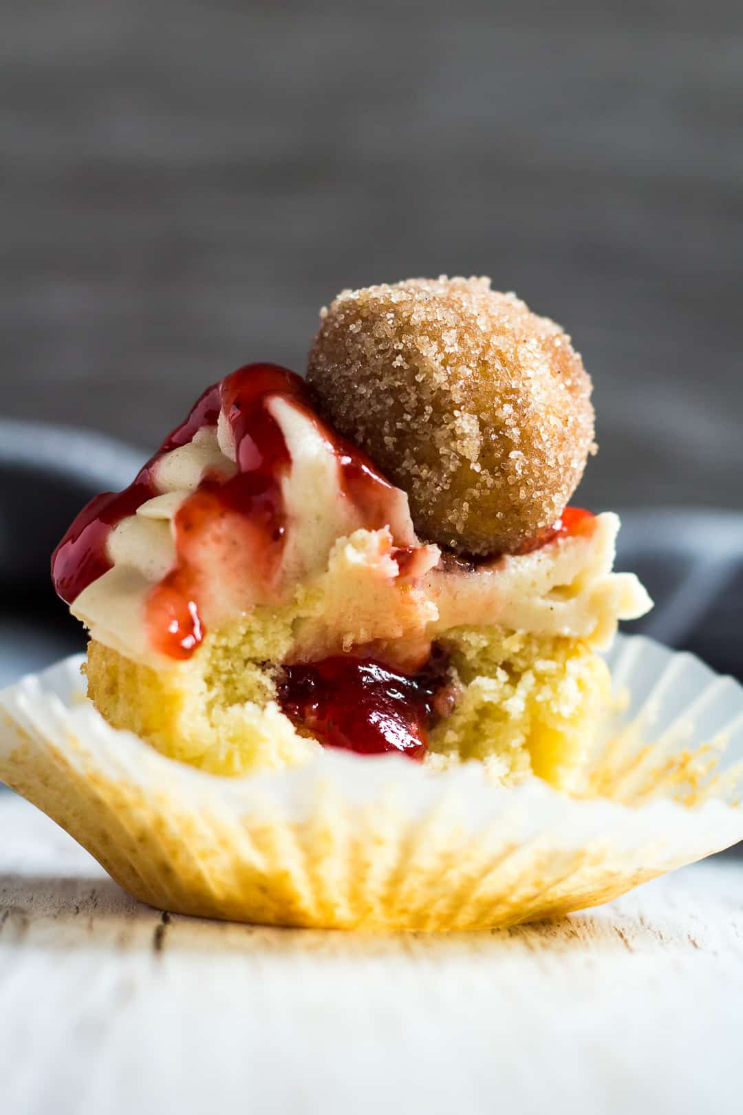 A jam doughnut cupcake with a bite taken out of it to show jam filling.