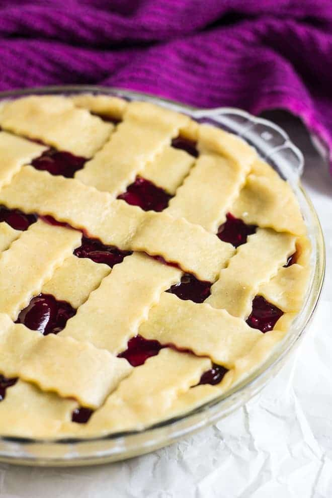 Glass pie dish lined with homemade pie crust dough with cherry filling and lattice top.