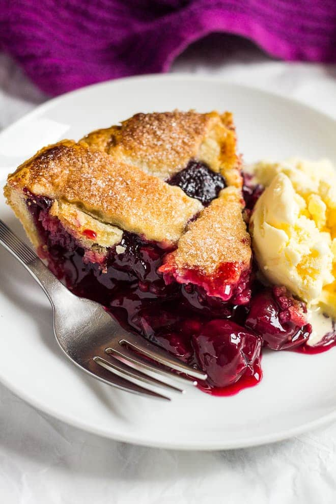 A slice of homemade cherry pie served on a small white plate with ice cream and a fork.