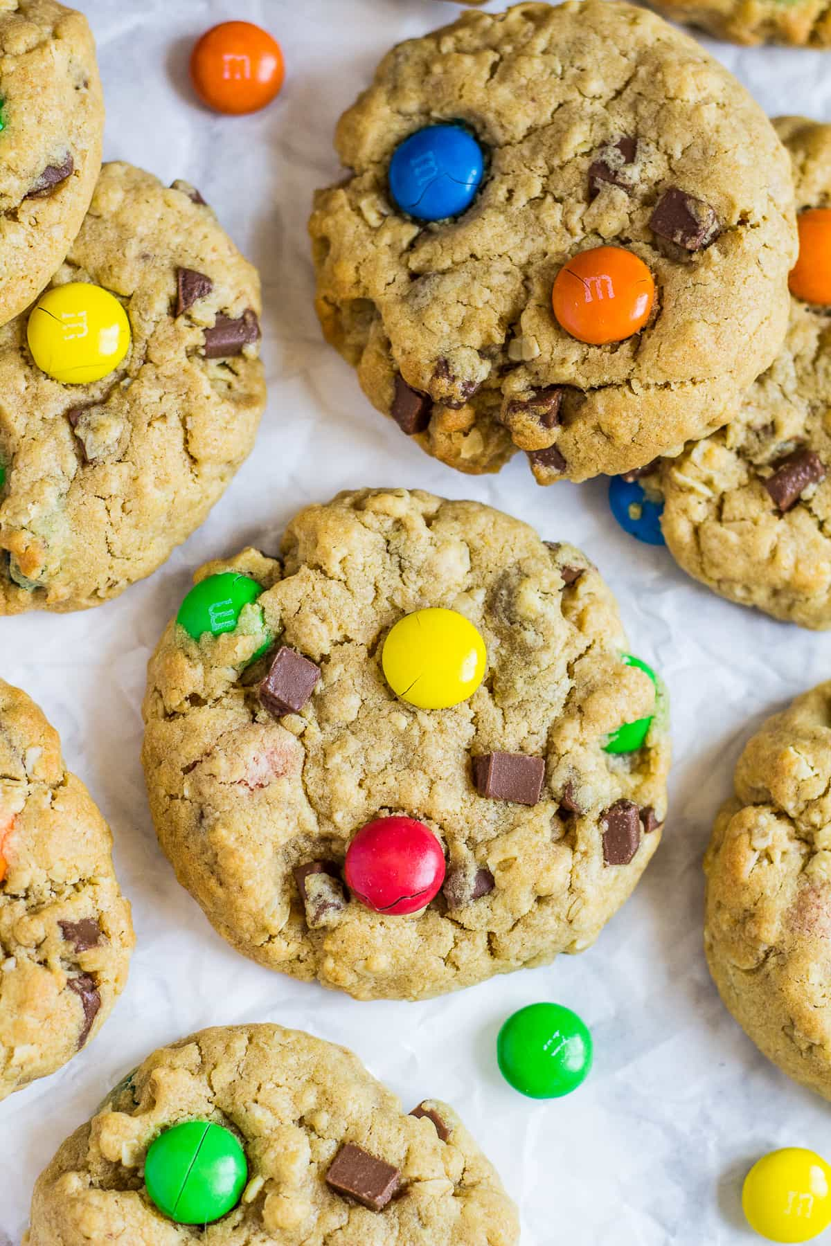 Close-up of monster cookies with M&Ms on parchment paper.