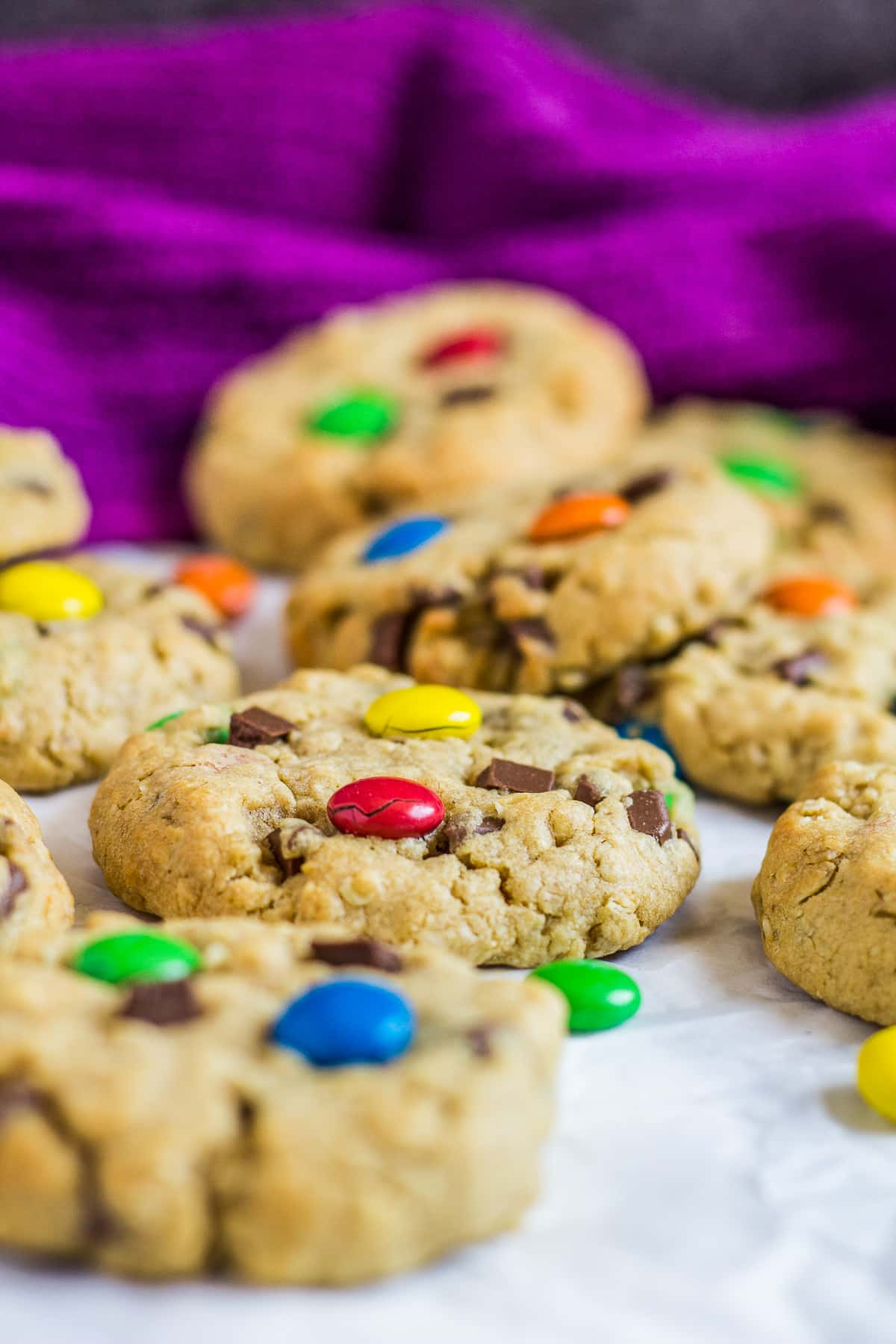 Side-view shot of thick monster cookies with M&Ms on parchment paper.