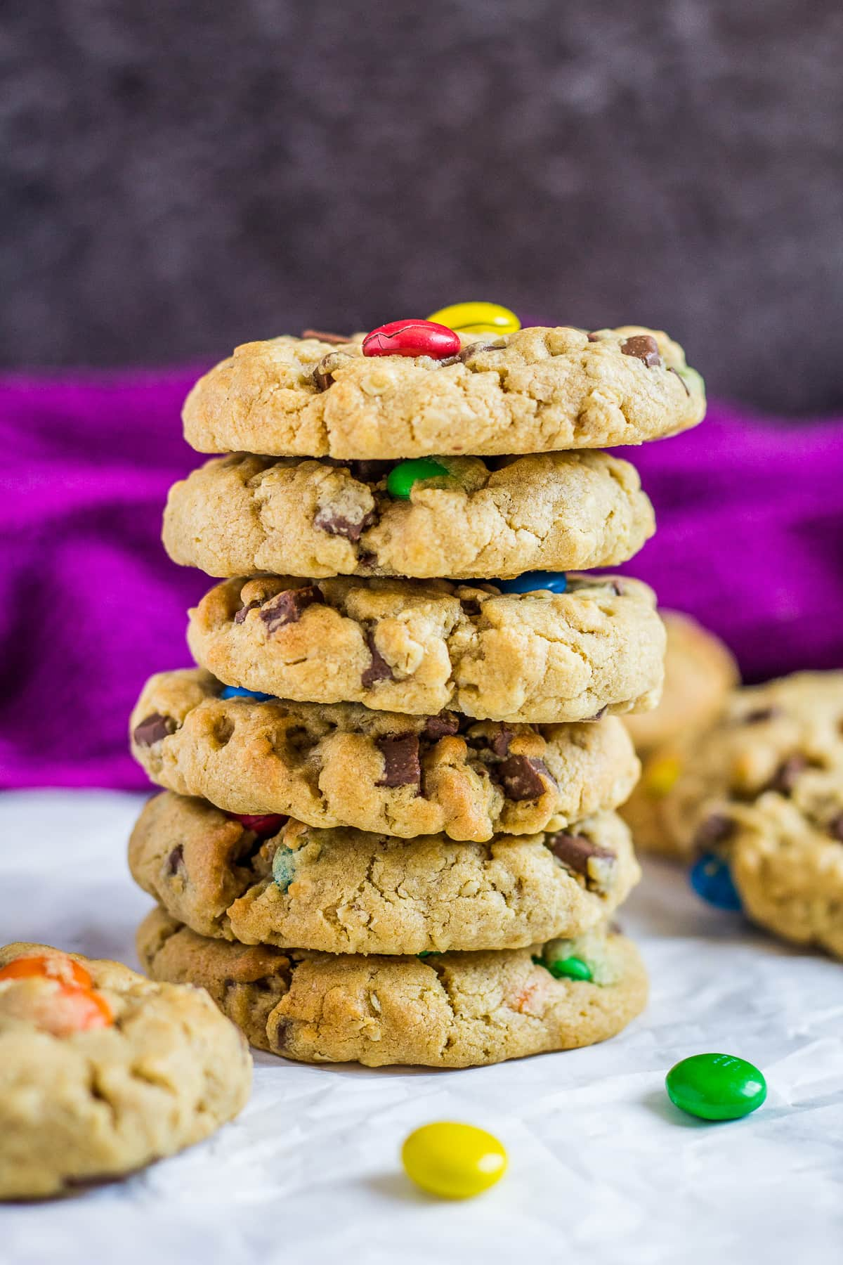 A tall stack of monster cookies with M&Ms on parchment paper.