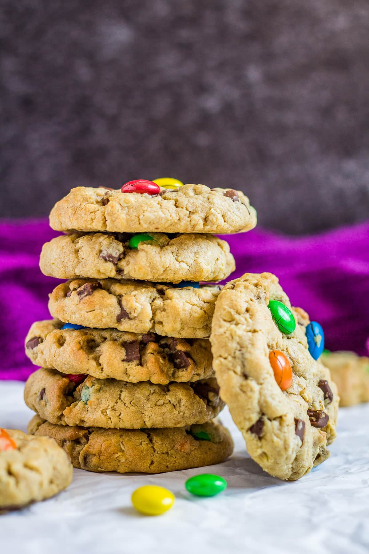 A stack of monster cookies with M&Ms on parchment paper.