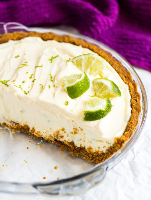 Half of a no-bake key lime pie in a glass pie dish topped with lime slices.