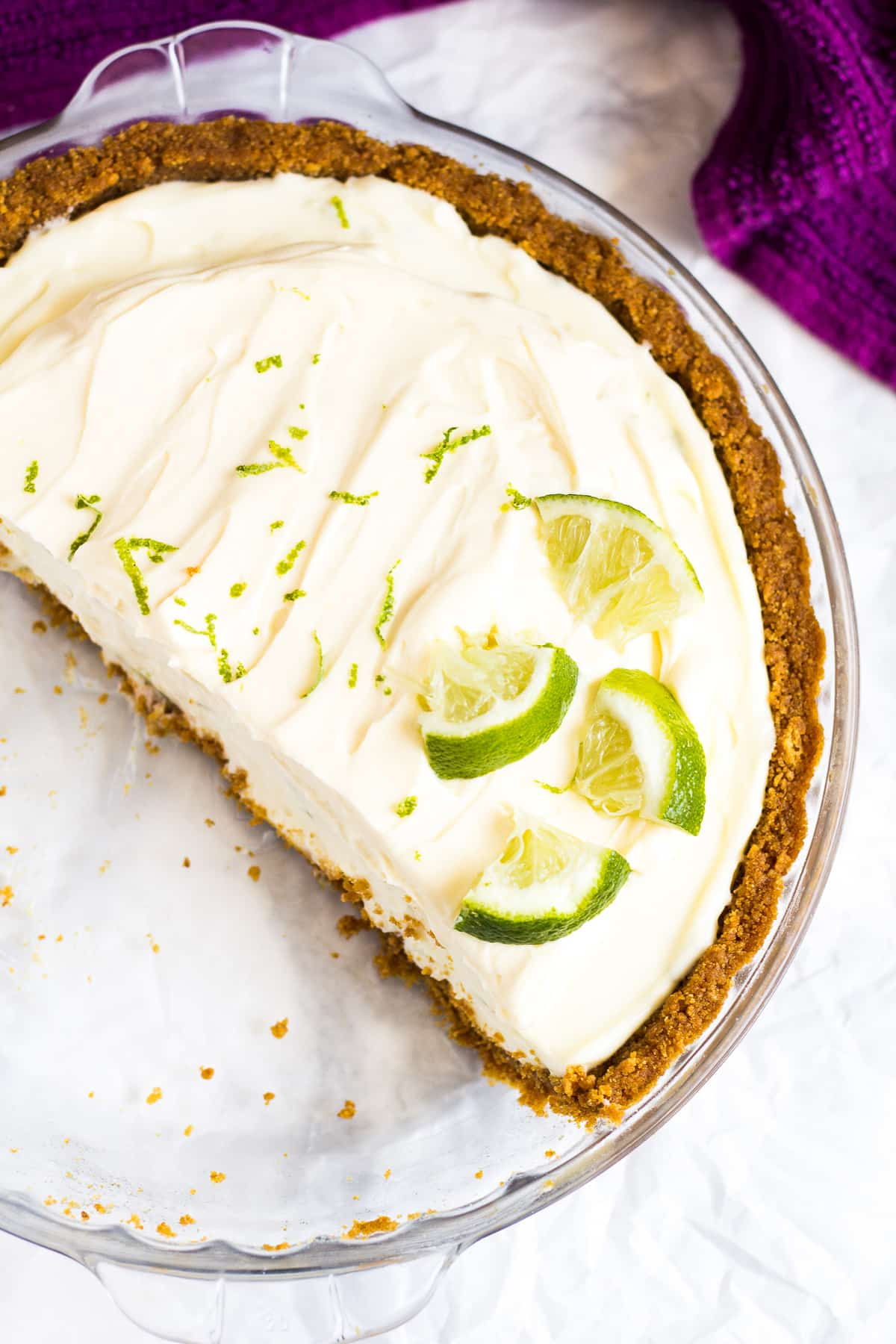 Overhead shot of half of a no-bake key lime pie in a glass pie dish.