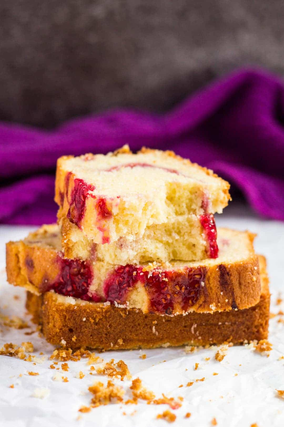 A stack of raspberry swirl lemon pound cake slices with the top slice cut in half.