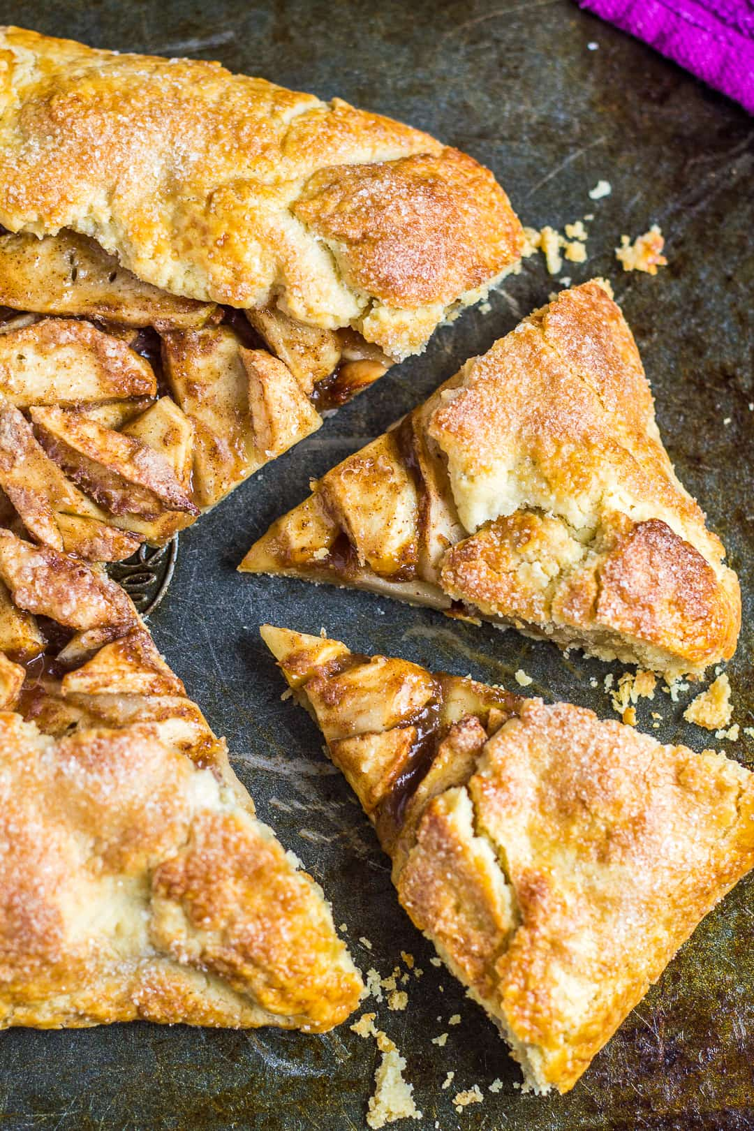 Overhead shot of homemade apple galette with two slices cut out on a baking tray.