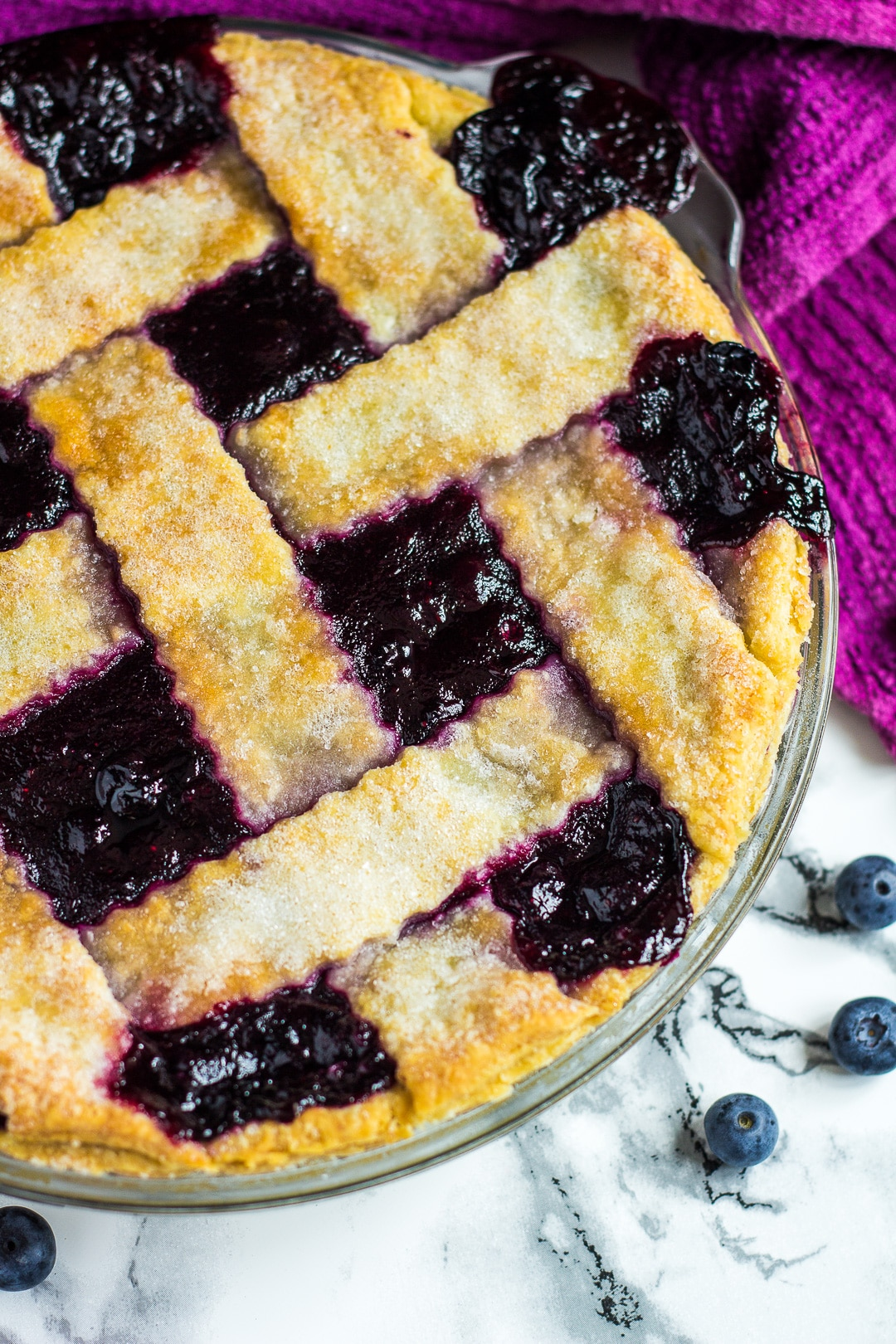 Overhead shot of a homemade blueberry pie in a glass pie dish.