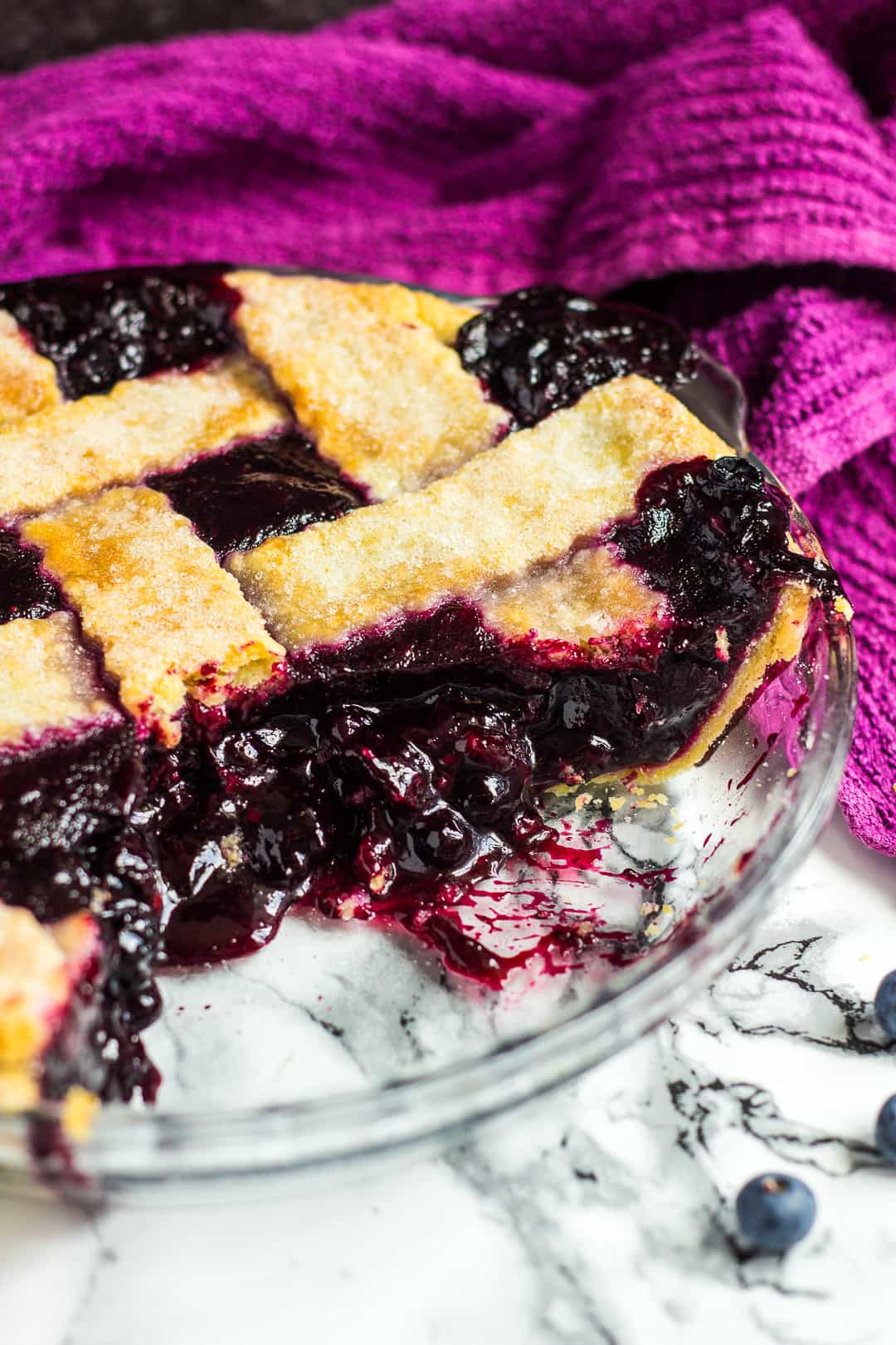 Homemade blueberry pie with slices removed to see the blueberry filling.